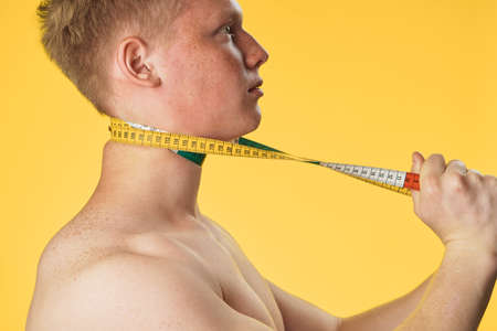 A sporty man with a body meter, a man of sporty appearance on a yellow background. Stock Photo