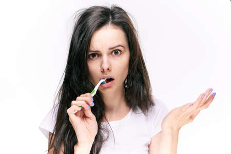 Woman brushes teeth on isolated background portrait.