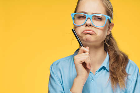 Frustrated woman, a woman in glasses holds a pen on a yellow background. 免版税图像