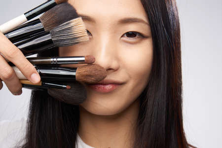 techniek: Beautiful asian woman holding a cometic brush portrait on a gray background.