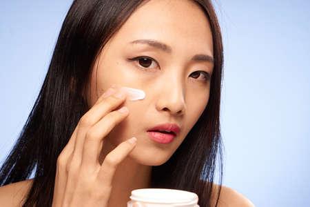 女性は、顔、青の背景に顔の手入れにクリームを置きます。 写真素材