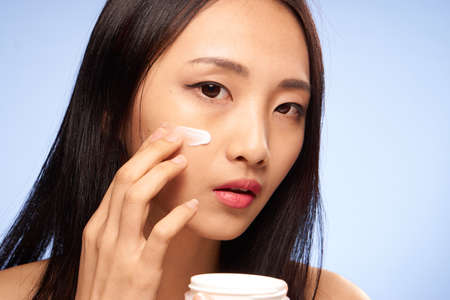 Woman puts cream on face, face care on blue background.