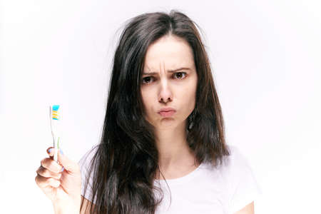 Teeth care, woman holding a toothbrush, toothbrush, healthy teeth, a woman rinses her mouth on an isolated background. Stockfoto