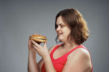 Hungry woman looking at a hamburger, woman with a hamburger on a gray background.