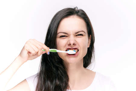 Woman brushing her teeth after eating on isolated background.