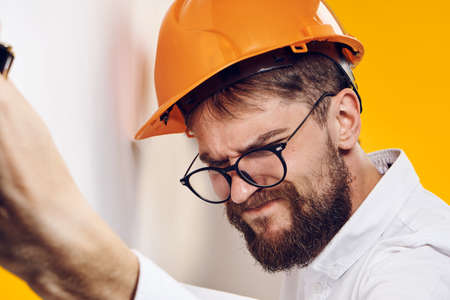 hard: Businessman in hard hat, businessman in glasses, businessman with blueprint on yellow background Stock Photo