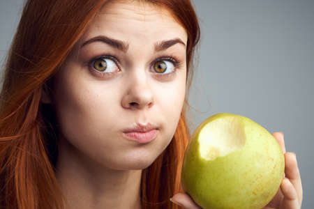 Diet, vitamins A, B, C woman eating an apple, a woman took a bite of an apple and acer portrait background. Stock Photo
