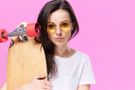 building feature: Woman in glasses, sportswoman, woman with skateboard, woman on pink background.