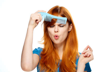 Woman with comb, woman combing her hair, woman on isolated background. Stock Photo
