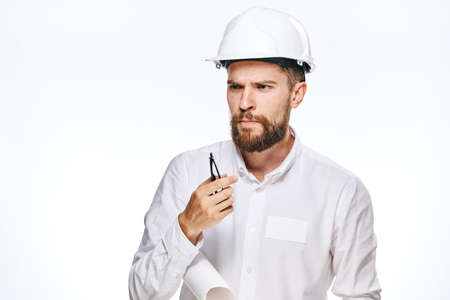 hard: Businessman thoughtful, businessman in hard hat, businessman with blueprint on light background.