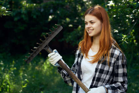 pitchfork: Woman with a rake, woman in a garden. Stock Photo