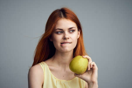 Woman with apple, healthy diet, apple, diet, woman reflected on gray background.