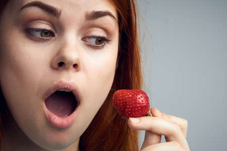 undergarments: Woman is looking surprised at a strawberry, a woman is holding a strawberry on a gray background portrait.