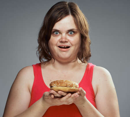 Fast food, slimming, hamburger, a woman holding a hamburger, a woman on a gray background.