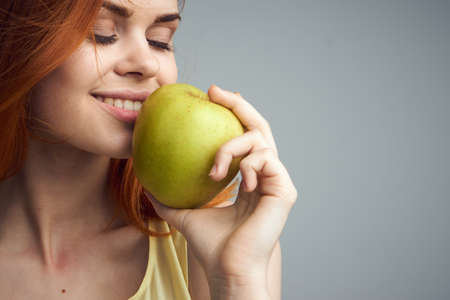 Diet, slimming, smile, health, beauty, nutrition, apple, girl with apple, girl on gray background.