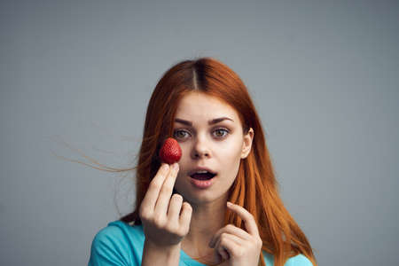 convicts: Strawberry, summer, season, sweets, sweet strawberry, girl on a gray background. Stock Photo
