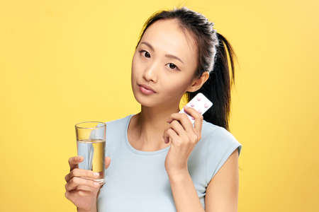 Asian, pill, glass of water, girl holding pills, health, illness, treatment, girl on yellow background.
