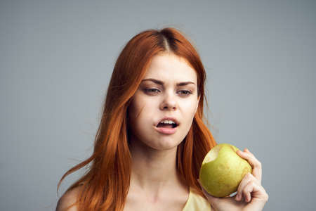 Girl eating an apple, diet, girl on a gray background, beauty, health.