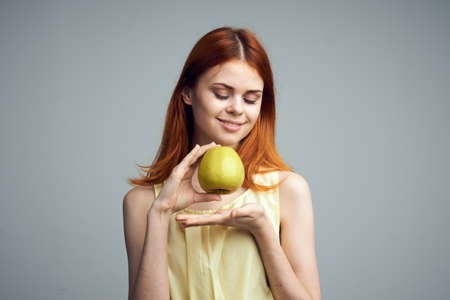 convicts: Diet, fruit, girl holding an apple on a gray background, beautiful young woman with red hair. Stock Photo