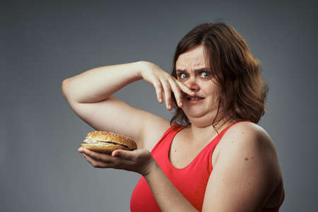stinks: Harmful food, hamburger, hamburger stinks, woman with a hamburger, woman on a gray background. Stock Photo