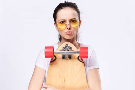 Woman with glasses, sport, woman with skateboard, woman on light background.