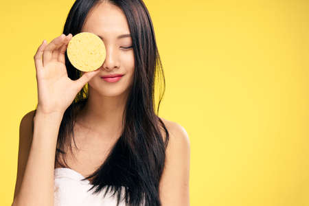 Skin care, woman with sponge, sponge, woman on yellow background portrait.