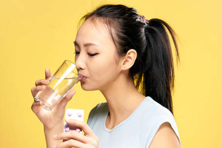 Woman sick, health, woman drinks a pill, pill, glass of water, woman on a yellow background.