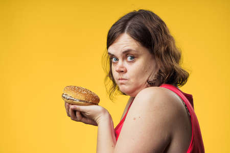 Fat, woman on a yellow background holds a hamburger, fast food, diet. Stock Photo