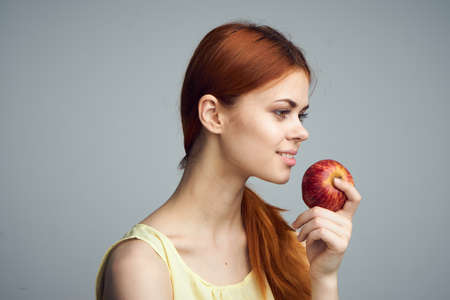 Fruit, summer, nutrition, food, girl on a gray background holds an apple, beauty, health. Stock Photo