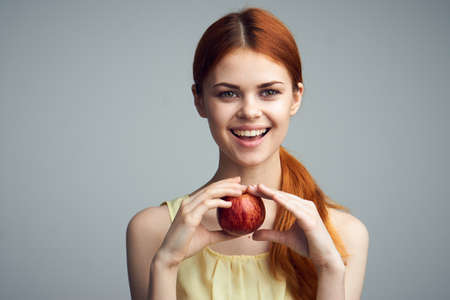 Smile, laugh, fruit, food, diet, beauty, health, nutrition, woman on a gray background holding an apple. Stock Photo