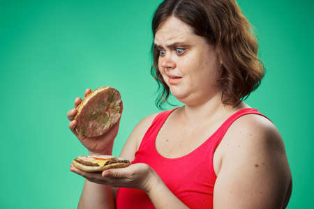 Hungry woman, harmful food, hamburger, woman with a hamburger, woman on a green background.
