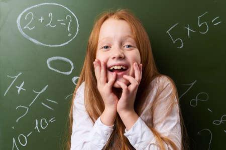 Joyful schoolgirl, girl with a smile, schoolgirl on the background of a school board. Standard-Bild