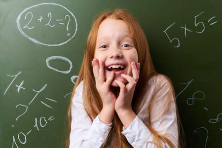 Joyful schoolgirl, girl with a smile, schoolgirl on the background of a school board. Stock Photo