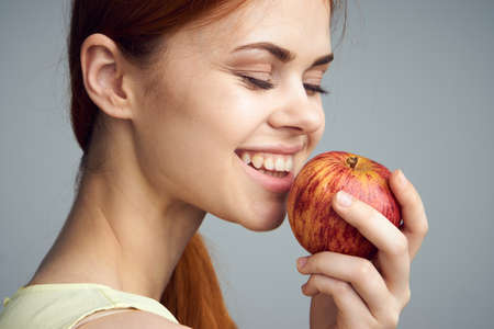 Smile, woman on a gray background holds an apple, fruit, diet, healthy food, health, beauty.