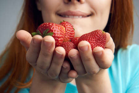 Strawberry, berries, sweetness, fruit, food, emotions, woman on a light background.