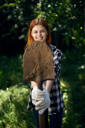 Woman in the garden holds a shovel, smile, summer, gardener.