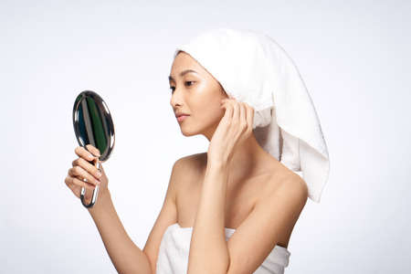 Natural beauty, woman in a towel looking in the mirror on a white background, asian.
