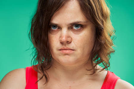 Emotions, fat, diet, portrait, woman on a green background, discontent. Stock Photo