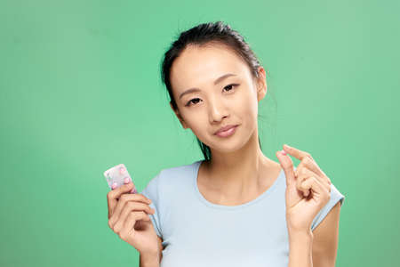 Asian, woman on green background holds a pill, capsule, pharmacy, treatment, illness.
