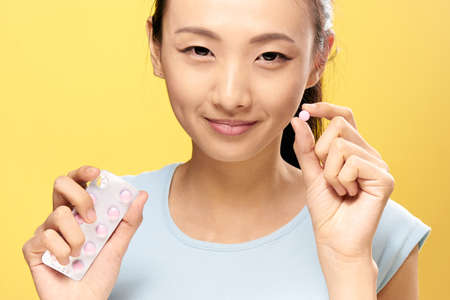 Asian, woman on a yellow background holds a pill, pharmacy, treatment. Stock Photo