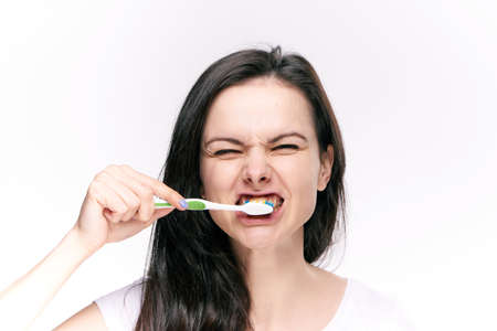 woman on white isolated background brushes teeth, toothbrush. Stockfoto