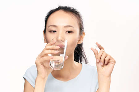 Young woman on white isolated background holds a pill, capsule, pharmacy, formateutics,Asian.