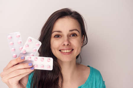 Young woman on a white background holds a pack of pills, pharmaceuticals. Stock Photo