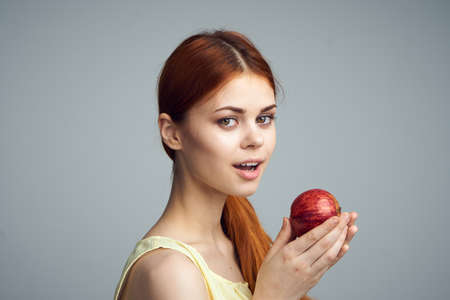 Young beautiful woman on a gray background holds an apple, fruit, diet. Stock Photo
