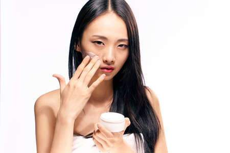 only 1 woman: Asian, woman on White isolated background applies cosmetic face cream.