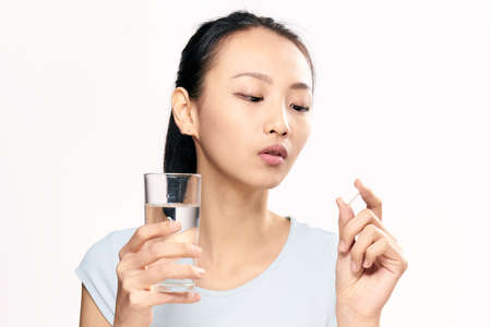 Young woman on a White isolated background holds a tablet, pharmacy,Asian.