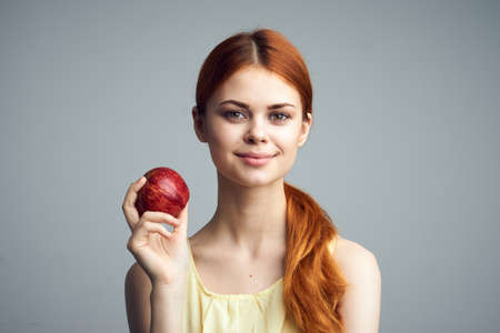 convicts: Young beautiful woman on a gray background holds an apple.