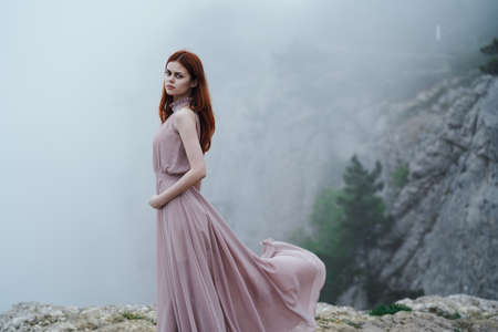 Beautiful young woman in a long dress in the mountains.