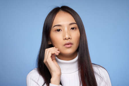 Beautiful young woman on a blue background, portrait, asian.