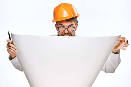 religious clothing: Engineer on white isolated background holds a blueprint, builder. Stock Photo